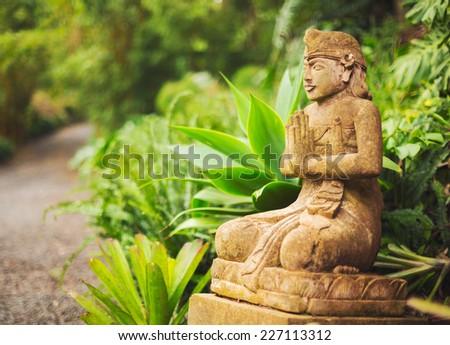 Buddhist Statue on Tropical Estate in the Jungle - stock photo