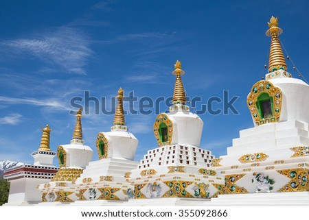 Buddhist white stupa and blue sky in the background in Thiksey Monastery in Leh , Ladakh, India. Close up - stock photo