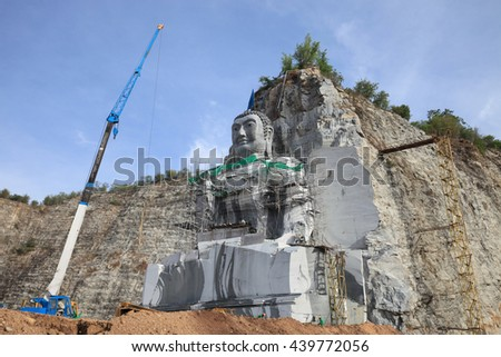 Buddhists in Thailand are carved marble mountain is shaped like the Buddha meditating. - stock photo
