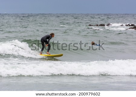 BUDE, CORNWALL/UK - AUGUST 13 : Surfing at Bude in Cornwall on August 13, 2013. Unidentified women