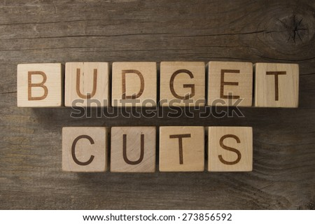 budget cuts text on a wooden background