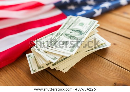 budget, finance and nationalism concept - close up of american flag and dollar cash money on wood