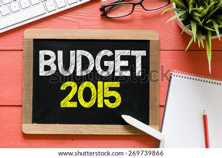 Budget 2015 Handwritten on blackboard. Budget 2015 Handwritten with chalk on blackboard, keyboard,notebook,glasses and green plant on wooden background - stock photo