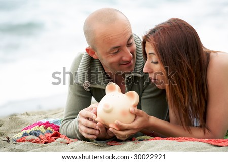Budget holidays - young couple holding a piggy bank - stock photo