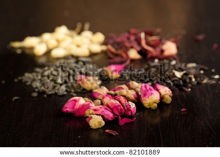 Buds of dried roses with dry tea as background on black - stock photo
