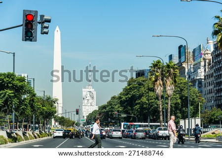 Buenos Aires, Argentina - April 9, 2015: Unidentified business people walking down the street at iconic building  Obelisco on April 9, 2015 in Buenos Aires, Argentina - stock photo
