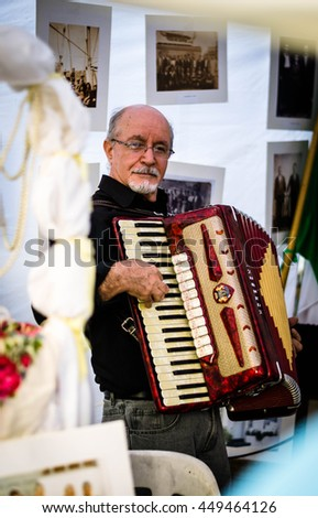 BUENOS AIRES, ARGENTINA - APRIL 2, 2016: Unidentified man playing accordion at a street fair dedicated to Calabrian culture - stock photo