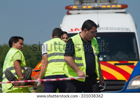 Buenos Aires, Argentina - Oct 22, 2015: Emergency ambulance team transporting accident victim on stretcher providing first aid on the road. - stock photo