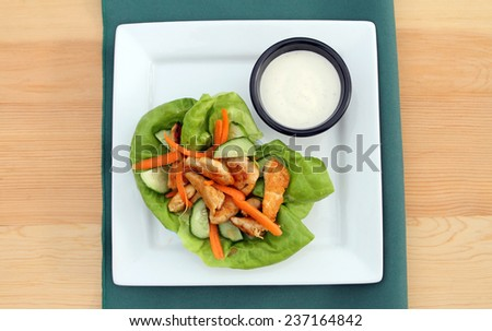 Buffalo chicken lettuce wrap, with spicy chicken, cucumbers, carrots, lettuce and dipping sauce. - stock photo