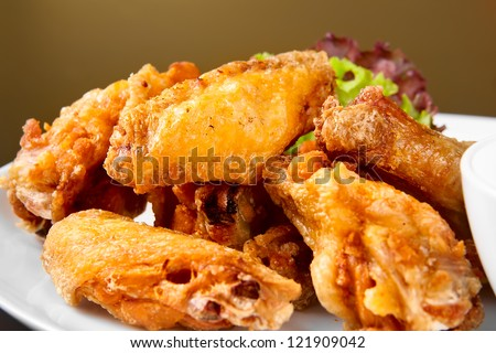 Buffalo chicken wings on plate with sauce - stock photo