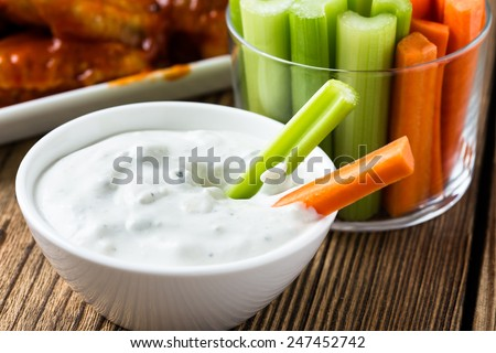 Buffalo chicken wings with cayenne pepper  sauce served hot with celery sticks and carrot sticks with blue cheese dressing for dipping - stock photo