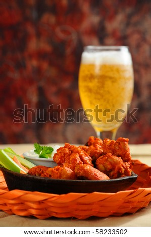 Buffalo style chicken wings served with cold beer. - stock photo