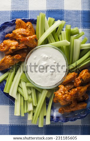 Buffalo wings with blue cheese dressing and celery sticks.
