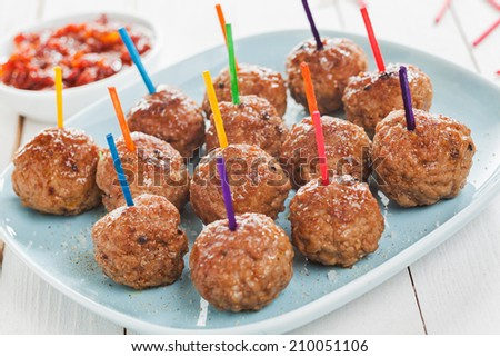 Buffet display of tasty spicy meatballs with colorful toothpicks for dipping arranged on a plate - stock photo