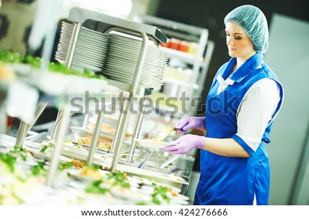 buffet female worker servicing food in cafeteria - stock photo