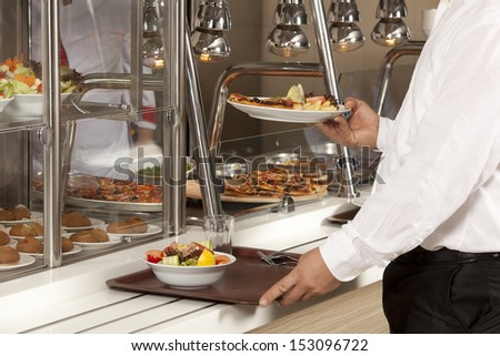 buffet self-service food display human hand take plate - stock photo