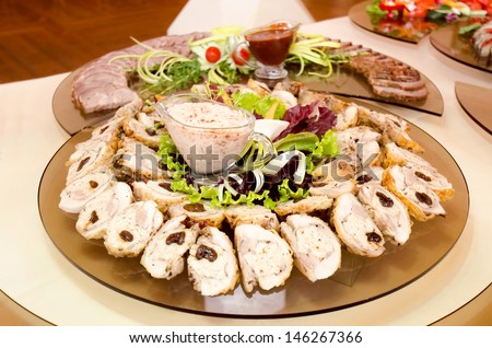 Buffet table displayed with glass platters of cold meats with dips in the center at a celebration, reception or luxury catered event