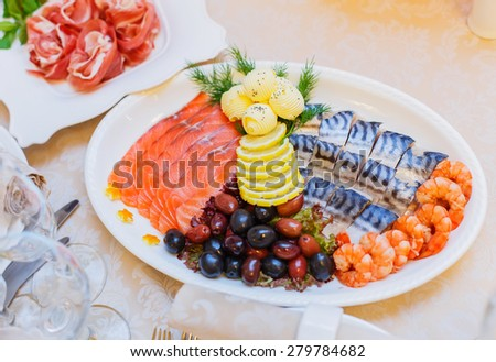 Buffet table served with mediterranean food. Assorted fish, smoked fish, salmon, herring, shrimp, black and green olives - stock photo
