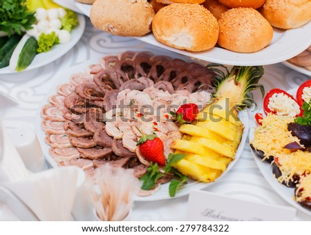 Buffet table served with tasty meals. Assorted meat, stuffed chicken roll, ham with mushrooms and greens decorated with fruit - stock photo