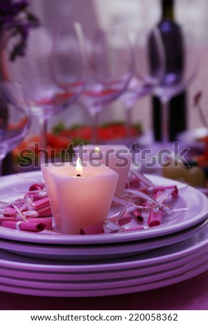 Buffet table with dishware and candles waiting for guests - stock photo