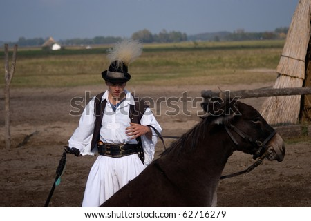 BUGAC, HUNGARY - OCTOBER 8 : Hungarian horseman participates in the local Bugac Festival October 8, 2010 in Bugac, Hungary. He wears the traditional Hungarian national costume for the horse show.