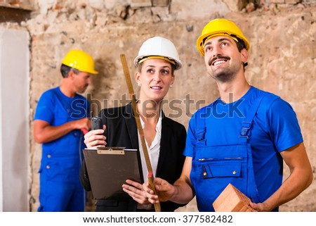 Builder and architect discussing on construction site, he is holding a folding rule pointing with it - stock photo