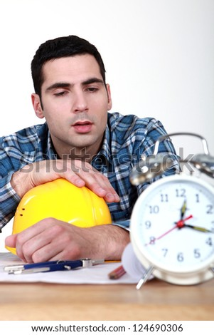 Builder being woken up by alarm clock - stock photo