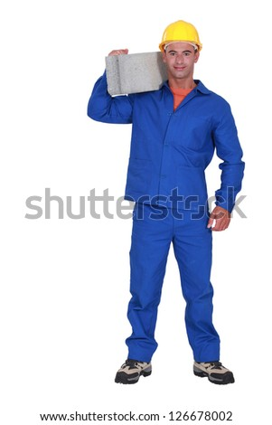 Builder carrying a concrete block - stock photo