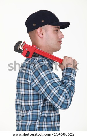 Builder carrying wrench - stock photo