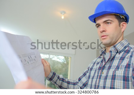 Builder checking the floor plans - stock photo