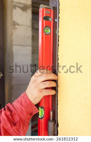 Builder ensuring that a door is vertical holding a builders level against the door as he installs it on a new building during construction - stock photo
