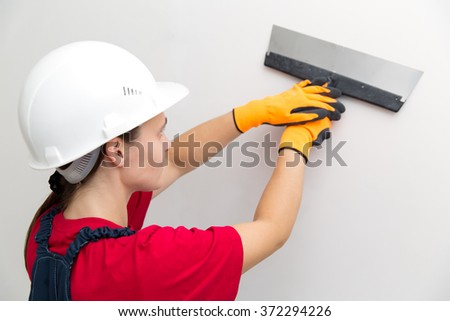 Builder female indoor worker plastering wall with spatula trowel tool  - stock photo