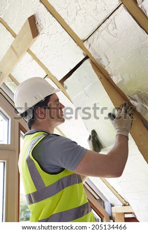 Builder Fitting Insulation Boards Into Roof Of New Home - stock photo
