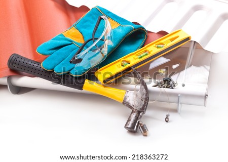 Builder hammer, gloves, glasses, level, screws and roof made �¢??�¢??of polycarbonate - stock photo