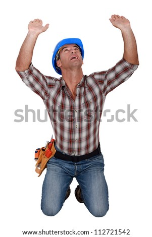 Builder holding up invisible object - stock photo
