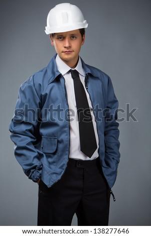 builder in a blue jacket, helmet in hand pocket - stock photo