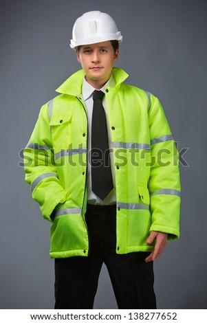builder in a green jacket, helmet in hand pocket - stock photo