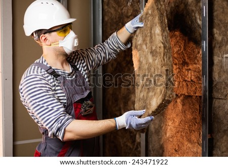 Builder in protective wear applying material on a wall - stock photo