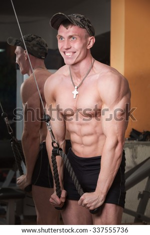 builder in the gym pumping iron and smiling
