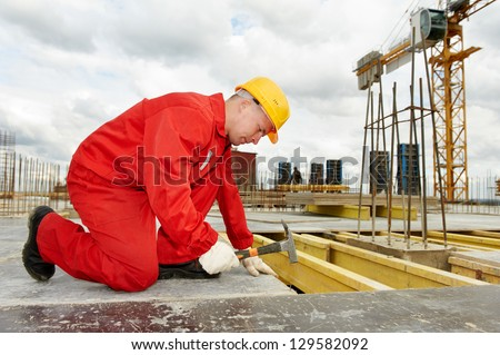 builder in uniform working with hammer and nail at construction site - stock photo