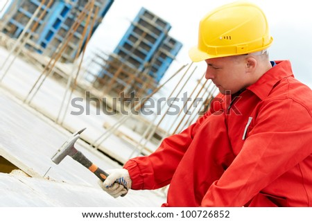 builder in uniform working with hammer and nail at roofing construction site