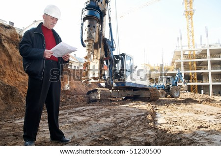 builder inspector worker at construction site with documentation - stock photo