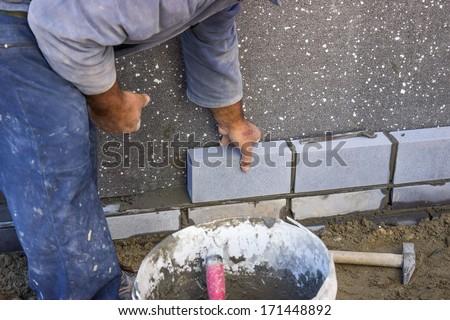builder laying bricks, constructing a wall  at construction site  - stock photo