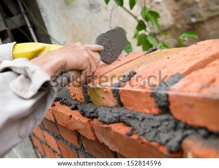builder laying bricks in site. - stock photo