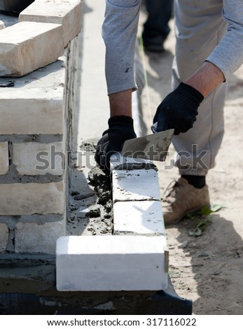 Builder lays Bricks in cement mortar - stock photo