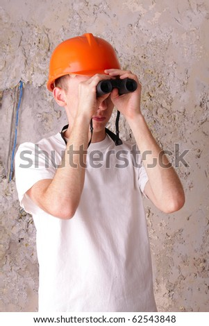 builder looking through binoculars at the background of the plastered walls - stock photo