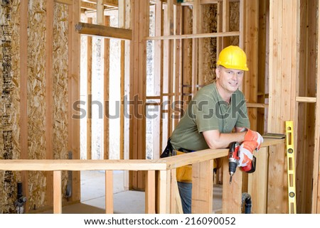 Builder on site in hardhat, smiling, portrait - stock photo