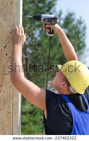 Builder or carpenter drilling a hole with a handheld electric drill in an upright wooden beam on a building site, close up side view - stock photo