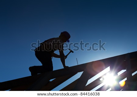 Builder or carpenter working on the roof - silhouette with strong back light - stock photo