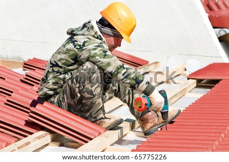 builder roofer working with screwdriver at roofing construction works - stock photo